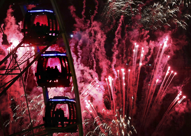 People ride a Ferris wheel as fireworks illuminate the sky over Edinburgh, Scotland, during New Year's eve celebrations late Tuesday Dec. 31, 2013.  The celebrations this year are combined with ma ...