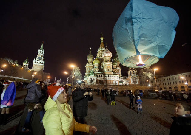 A woman launches a sky lantern during celebration for the New Year at the Red Square, in Moscow, Russia, early Wednesday, Jan. 1, 2014, with St. Basil Cathedral, centre right, and Kremlin's Spassk ...