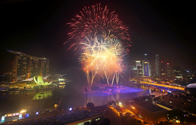 Fireworks explode over the financial district at midnight Wednesday in Singapore. Celebrations started on New Year's Eve where concerts were held and thousands gathered on the streets to usher in  ...