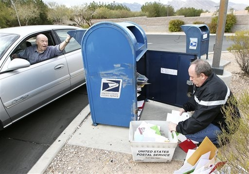 Jay Burt, of Las Vegas, left, places a letter in a mail drop box as postal employee Tim Watters empties it at the Summerlin branch of the U.S. Post Office in Las Vegas, Wednesday, Dec. 18, 2013. T ...