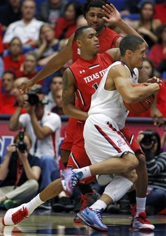 Arizona's Nick Johnson, center, hangs on to the ball as he drives to the basket against the defense of Texas Tech's Robert Turner, in the second half of an NCAA college basketball game on Tuesday, ...