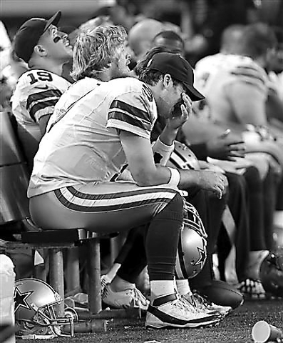 Dallas Cowboys quarterback Tony Romo sits on the bench in the final minutes of the second half of an NFL football game against the Green Bay Packers, Sunday, Dec. 15, 2013, in Arlington, Texas. Ro ...
