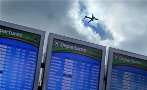 A plane takes off over a departure board at Hartsfield-Jackson Airport, Wednesday, Nov. 27, 2013, in Atlanta. Delta Airlines brought the University of Florida basketball team to Atlanta on Nov. 30 ...