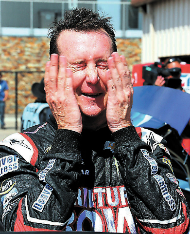 Kurt Busch wipes his face Saturday after practice for the NASCAR Sprint Cup Series race at Michigan International Speedway in Brooklyn, Mich. Busch placed third in Sunday's race and is ninth in t ...