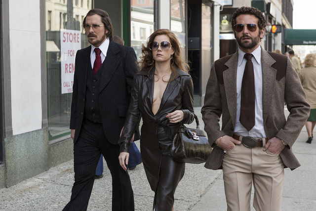 Irving Rosenfeld (Christian Bale), Sydney Prosser (Amy Adams) & Richie Dimaso (Bradley Cooper) walk down Lexington Ave. in Columbia Pictures' AMERICAN HUSTLE.  (Christian Bale suit, tie, shirt, gl ...