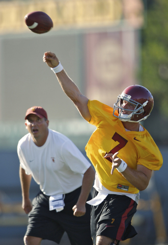 Southern California assistant coach Clay Helton, left, keeps an eye on quarterback Matt Barkley, during NCAA college football practice in Los Angeles on Wednesday, Aug. 4, 2010. (AP Photo/Damian D ...
