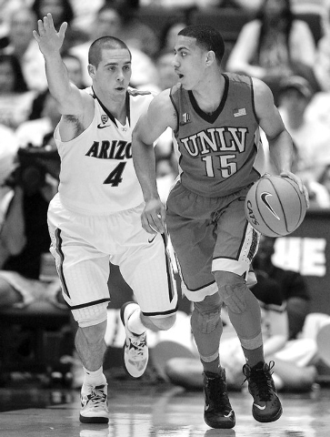 UNLV's Kendall Smith (15) dribbles away from Arizona's T.J. McConnell (4) in the first half of an NCAA college basketball game on Saturday, Dec. 7, 2013, in Tucson, Ariz. (AP Photo/John MIller)
