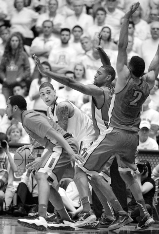 Arizona's Brandon Ashley, second from left, is surrounded by UNLV players as tries to pass in the second half of an NCAA college basketball game on Saturday, Dec. 7, 2013, in Tucson, Ariz. Arizona ...