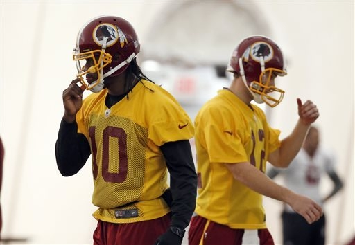Washington Redskins quarterbacks Robert Griffin III, left, and Kirk Cousins, work during their NFL football practice Wednesday, Dec. 11, 2013, in Ashburn, Va. Cousins will start for the Redskins o ...