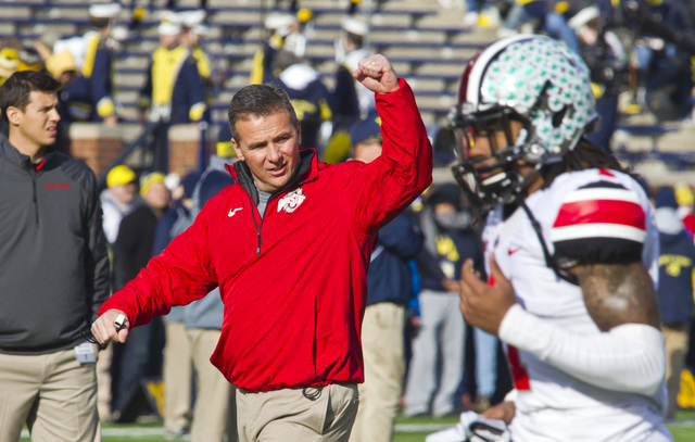 In this Nov. 30, 2013 file photo,  Ohio State head coach Urban Meyer responds to cheers from fans in Michigan Stadium as his team takes the field before an NCAA college football game against Michi ...