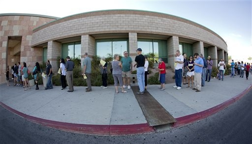 Las Vegas and Henderson, Nev. residents line up outside the Department of Motor Vehicles to renew vehicle registration and drivers licenses in this file photo. (AP Photo/Julie Jacobson)