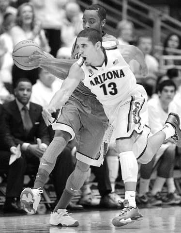 Arizona's Nick Johnson (13) tries to steal the ball away from UNLV's Kevin Olekaibe in the first half of an NCAA college basketball game on Saturday, Dec. 7, 2013, in Tucson, Ariz. (AP Photo/John  ...