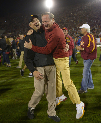 University of Southern California athletic director Pat Haden, right, jumps into the arms of Clay Helton, offensive coordinator and quarterbacks coach, after they defeated Stanford an NCAA college ...