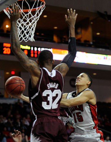 UNLV's Kendall Smith (15) lays up the ball against Mississippi State's Craig Sword during the first half of an NCAA college basketball game at the Las Vegas Classic at the Orleans Arena on Monday, ...