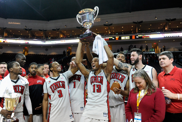 The UNLV basketball team with coach Dave Rice, right, celebrate with the championship trophy after defeating Mississippi State at an NCAA college basketball game at the Las Vegas Classic at the Or ...