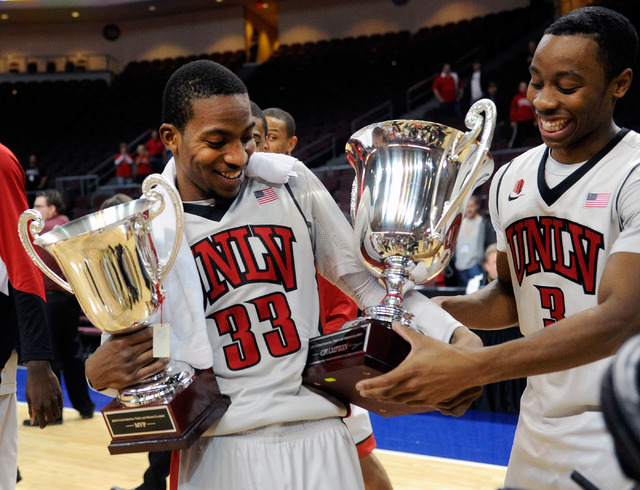 UNLV's Kevin Olekaibe (3) hands the championship trophy to teammate Deville Smith (33) as he holds the tournament MVP trophy after UNLV defeated Mississippi State at an NCAA college basketball gam ...