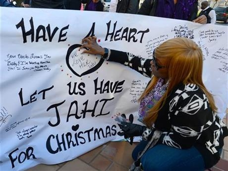 Dede Logan, of Oakland, adds red stars to a poster in support of Jahi McMath in front of Children's Hospital Oakland in Oakland, Calif., on Monday, Dec. 23, 2013. McMath was declared brain dead af ...