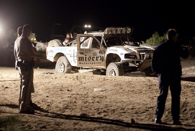 In this Aug. 14, 2010 file photo, law enforcement officers examine the accident scene where an off-road race truck, background, went out of control and plowed into a crowd of spectators during a r ...