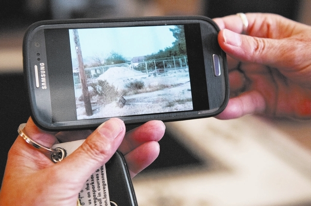 Laura Arnold, resident at the Elkhorn Ponderosa community in Las Vegas, shows a close up photo of the site where AT&T plans to build a cell tower near her home, Tuesday, Oct. 29, 2013. Arnold like ...