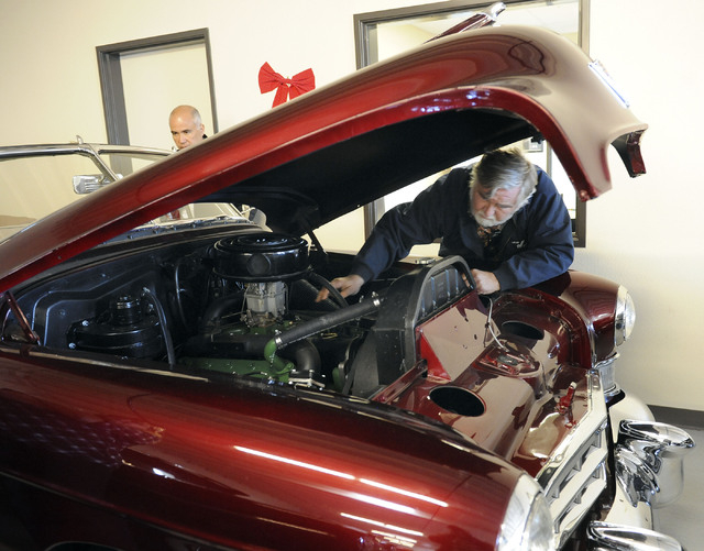 Jim Hill, of Fort Mojave, Ariz., looks at the engine of a 1948 Cadillac convertible as Mike Nicholl looks on at Classic & Collectable Cars in Las Vegas, Friday, Dec. 13, 2013. Nicholl, the owner o ...