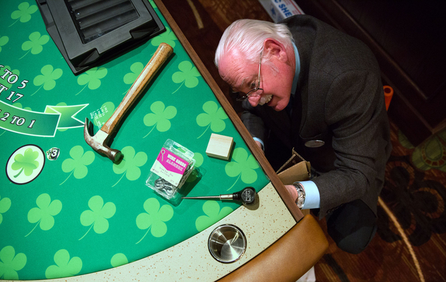 Richard Engel, table games supervisor at The Quad, prepares table games before the opening of O'Sheas Casino on Wednesday. O'Sheas, located inside The Quad, will reopen Friday, Dec. 27 at 9 a.m. i ...