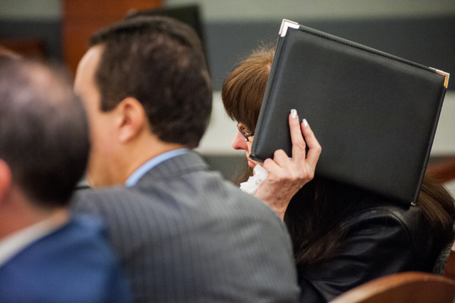Defendant Linda Cooney, right, covers her face from the media, during a hearing in which she is accused of shooting her son from the Regional Justice Center in Las Vegas Friday, Dec. 20, 2013. (Ma ...