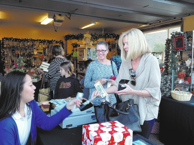 Cassandra Luong, far left, checks out shoppers Nov. 16 at the annual Cozy Cabin holiday fundraiser in a private home in northwest Las Vegas. Proceeds benefited 27 youngsters in need through Eagle  ...