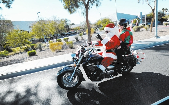 Chris Sylvia as Santa Claus and Tricia Rossol as his elf, cruise down N. Rancho Drive in Las Vegas on his motorcycle on Sunday, Dec. 22, 2013. The couple had no particular destination, but just wa ...
