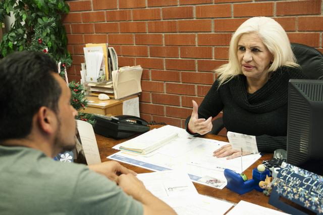 Esperanza Montelongo, right, owner of Aztec Insurance, discusses auto services with client Porfirio Mora at her office in Las Vegas Saturday, Dec. 28, 2013. (Erik Verduzco/Las Vegas Review-Journal)