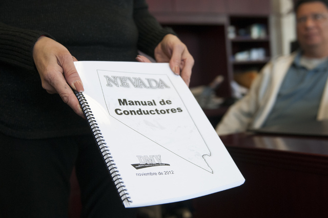 Esperanza Montelongo, owner of Aztec Insurance, shows a DMV driver's manual written in spanish at her office in Las Vegas Saturday, Dec. 28, 2013. Montelongo's office is hosting classes on how to  ...