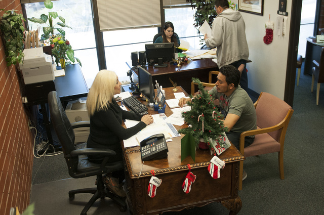 Esperanza Montelongo, left, owner of Aztec Insurance, discusses auto services with client Porfirio Mora at her office in Las Vegas Saturday, Dec. 28, 2013. (Erik Verduzco/Las Vegas Review-Journal)