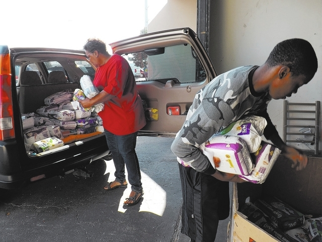 Marie Tims, left, from the Women's Resource Medical Centers of Southern Nevada and volunteer Ray Johnson load Tims car with diapers and baby wipes at the Back 2 Basic Global Outreach warehouse, 44 ...