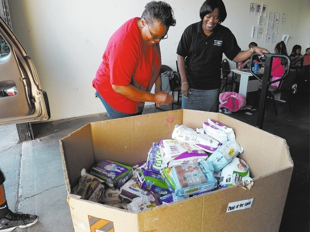 Marie Tims, left, from the Women's Resource Medical Centers of Southern Nevada and the Rev. LaDonna Tapplin, right, load Tims car with diapers and baby wipes at the Back 2 Basic Global Outreach wa ...