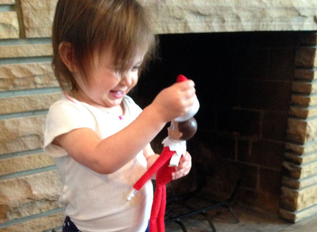 Carly Kerby's 18 month-old daughter, Mati, plays with a felt elf at their home in Salt Lake City. The Elf on the Shelf serves as a scout for Santa and has to be moved stealthily every night, tradi ...