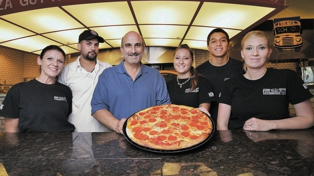 Sam Facchini, co-founder and co-owner of Metro Pizza, third from left, poses with employees, from left, Krista Hollis, Edgar Padilla, Bailey Vreeland, Keoni Sakai and Erin Kalteich at the pizzeria ...