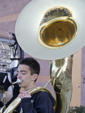 Part of the crowd is reflected in sophomore D. J. Watts' Sousaphone bell at the groundbreaking ceremony for the Crusader Competition Complex, the new 1,150-seat athletic center at Faith Lutheran M ...