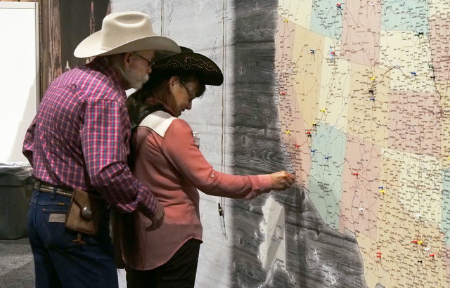 Lee And Cathy Smith, of Jamul, Calif., place a pin on their town on a U.S. map at the National Finals Rodeo FanFest in the Las Vegas Convention Center, Thursday, Dec. 5, 2013.  (Jerry Henkel/Las V ...