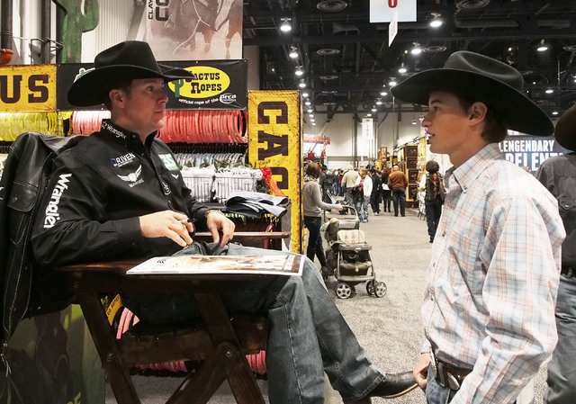 National Finals Rodeo all-around cowboy champion Trevor Brazile, left, talks with Mason Mileski, of Ogden, Utah, as he signs an autograph at the NFR Cowboy Christmas Gift Show in the Las Vegas Con ...