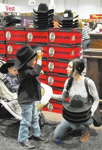 Lindsay Branquinho, of Los Alamos, Calif., watches as her son, Cade, 5, tries on hats at the Teskey's booth at the National Finals Rodeo Cowboy Christmas Gift Show in the Las Vegas Convention Cent ...