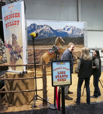 Jonathan Adams, of Kentucky, left, talks with Penny Gilley, center, and April Cashion at a booth where fans can get a photo taken with Roy Rogers' horse Trigger, background, at the National Finals ...