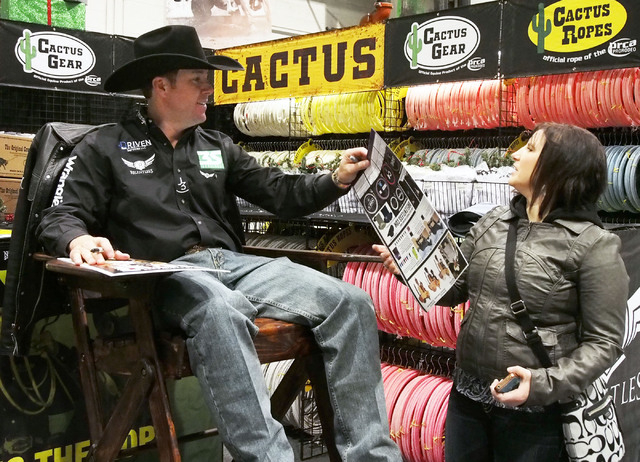 National Finals Rodeo all-around cowboy champion Trevor Brazile signs an autograph for Krista McKinney, of Edmonton, Alberta, Canada, at the NFR Cowboy Christmas Gift Show in the Las Vegas Convent ...