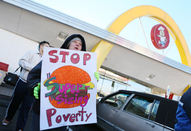 Heather Stephens holds a sign during a protest outside McDonald's on 2248 Paradise Road Thursday, Dec. 5, 2013, in Las Vegas. Stephens works at Taco Bell, is on welfare and provides for her ...
