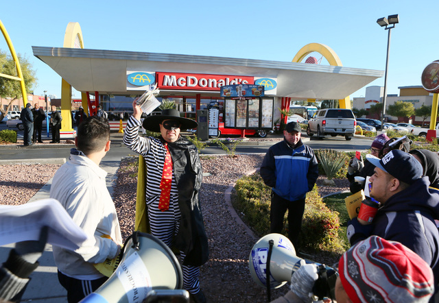 Javier Cabrera, center, who is dressed as McDonald's character Hamburglar, waves flyers that represented money during a protest outside McDonald's on 2248 Paradise Road Thursday, Dec ...