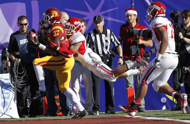 USC's Javorius Allen (37) drags a Fresno State defender in for a score during the Royal Purple Las Vegas Bowl at Sam Boyd Stadium in Las Vegas on Dec. 21, 2013. (Jason Bean/Las Vegas Review-Journal)