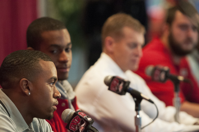 UNLV defensive back Kenneth Penny, left, reacts to his team's invitation to the Heart of Dallas Bowl during a press conference with teammates, seated from left, Caleb Herring, coach Bobby Hauck, B ...