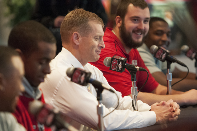 UNLV coach Bobby Hauck, center, speaks about his team's invitation to the Heart of Dallas Bowl during a press conference with his players, seated from left, Kenneth Penny, Caleb Herring, Brett Boy ...
