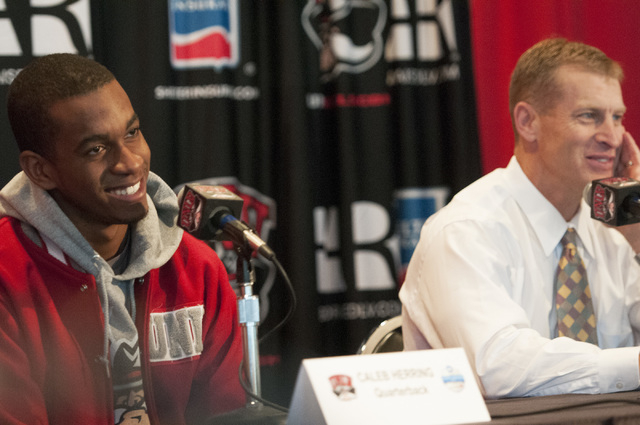 UNLV quarterback Caleb Herring, left, and coach Bobby Hauck react to their team's invitation to the Heart of Dallas Bowl during a press conference at Thomas & Mack Center in Las Vegas, Monday, Dec ...