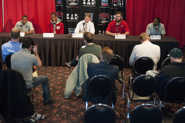 UNLV coach Bobby Hauck, center, and his players, seated from left, Kenneth Penny, Caleb Herring, Brett Boyko and Tyler Gaston, react to their team's invitation to the Heart of Dallas Bowl during a ...