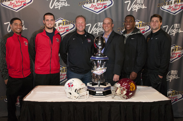 Fresno State quarterbacks, from left, Myles Carr, Derek Carr and head coach Tim DeRuyter, pose for a photo with University of Southern California interim head coach Clay Helton and quarterbacks De ...