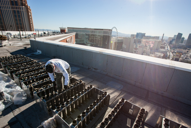 Pyrotechnician Henry Herman, of Fireworks by Grucci, loads in fireworks for the finale during preparation of the New Year's Eve fireworks show on the roof of the Treasure Island in Las Vegas on Mo ...